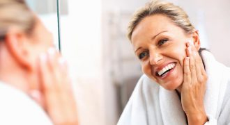 woman looking in mirror smiling | skin rejuvenation